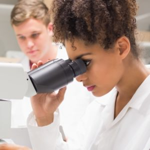High school student looking into a microscope